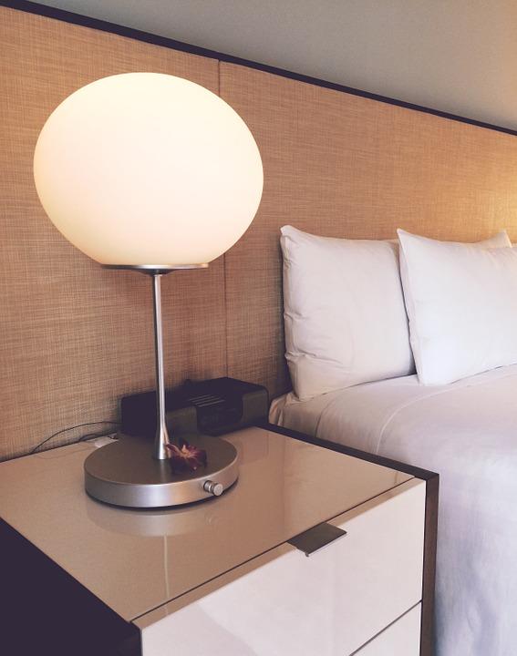 Białe szafki nocne z połyskiem w sypialni